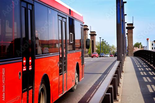 Plakat Samochody miejskie na moście. Ruch uliczny z czerwonym autobusem. Transport publiczny.