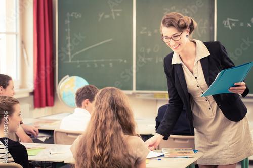 Fotografía  Lehrer teilt Arbeit an Klasse in Schule aus
