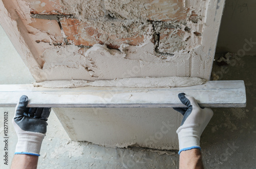 Worker is putting a gypsum plaste.