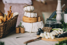 A Pile Of Cheese Heads In A Paper, Next A Sliced Cheese, Basket Of Bread And Grapes, Wine And Plant Plugs