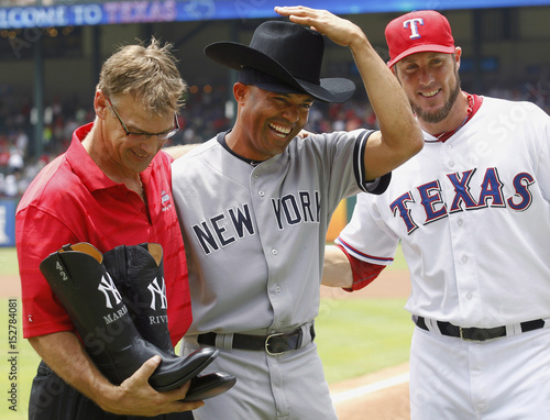 a8a217cef46f4 Yankees pitcher Rivera is presented with a cowboy hat from Rangers closer  Nathan and a pair of boots ...