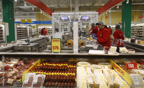 Employees prepare cheese at grocery store which is 100th