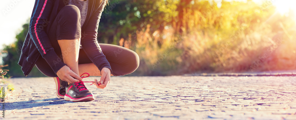 Fototapeta Runner Woman Tying Her Shoelaces While Jogging - Sport And Fitness At Sunset