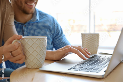 Young couple with laptop at home, closeup