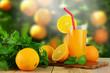 Orange juice with oranges and blurred garden background.