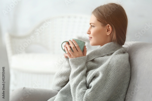 Foto  Beautiful young woman drinking tea while resting at home