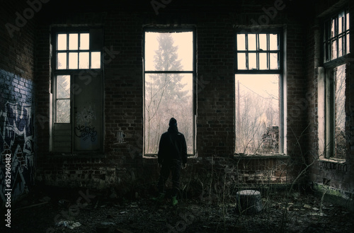 Foto op Plexiglas Oude verlaten gebouwen Lonely depressed man standing at dark abandoned factory.