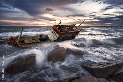 Photo sur Aluminium Naufrage Wrecked boat abandoned stand on rock beach