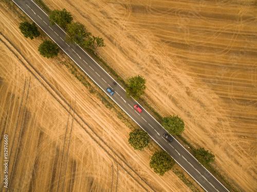 widok-z-lotu-ptaka-wiejskiej-drodze-posrod-pol-z-samochodem-na-nim