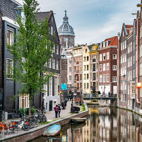 Valokuva  Amsterdam city view canal Singel with colorful dutch house, bridge, the Netherlands with Amstel river, Oudezijds Achterburgwal, reflection Basilica of St