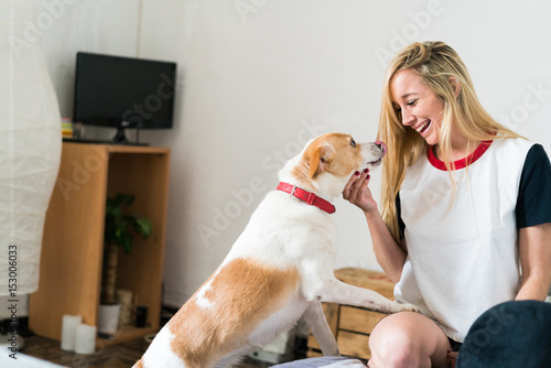 Sexy young woman at home playing with her dog
