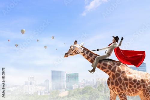 Photo  Businesswoman riding giraffe. Mixed media