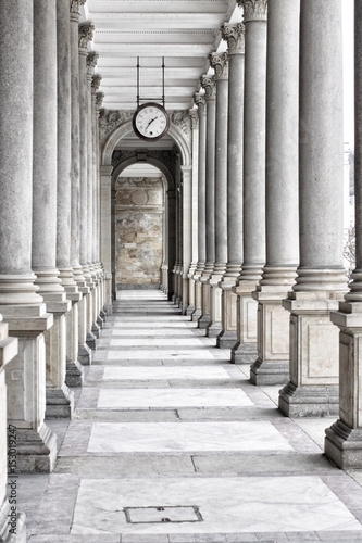 Fotografia  Colonnade of tall columns with clock by the ceiling