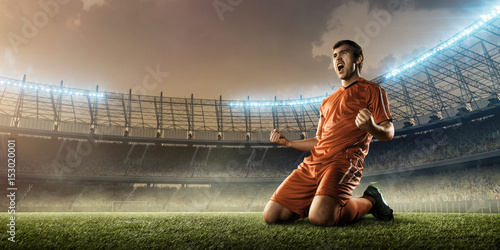 soccer player in red uniform celebrates a goal on a soccer field