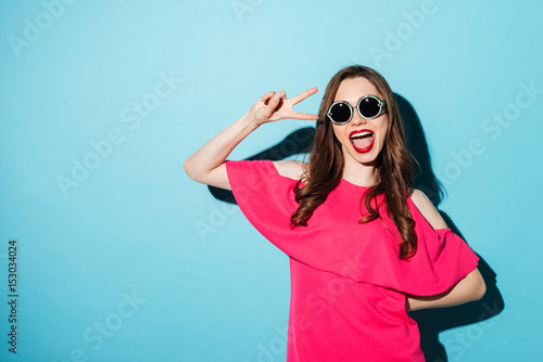Foto  Happy young brunette woman showing peace gesture