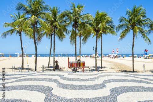 Photo Bright scenic view of Copacabana Beach with palm trees beside the iconic boardwa