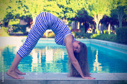 Fotografie, Obraz  Young woman in yoga asana near the pool toned