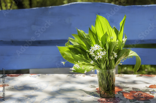 Fotografie, Obraz  A bouquet of simple spring wild gentle flowers in a glass cup on the table near the bench  in the garden