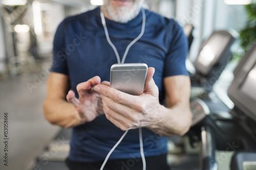 Senior man using smartphone in gym