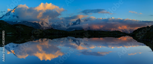 Poster Reflexion Mountains and clouds reflected in Lac De Cheserys, near Chamonix, France.