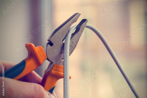 Photo Worker man cutting electric wires with pliers