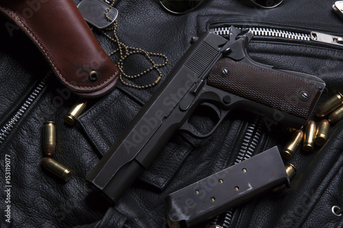 Gun Colt with bullets and holster  rests on a leather jacket Poster Mural XXL