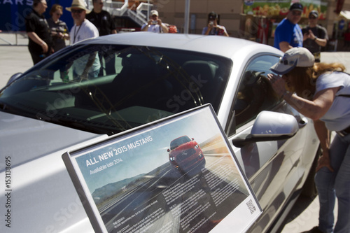 A woman looks into the redesigned 2015 Ford Mustang during