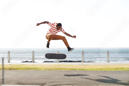 Skateboarder doing tricks and jumping on the road by the beach
