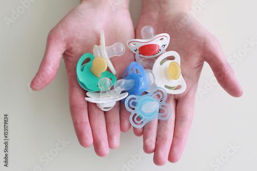 Valokuvatapetti Baby pacifiers in hands
