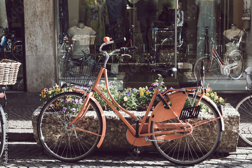 Deurstickers Fiets Retro vintage orange bike on cobblestone street in the old town. Old charming bicycle concept.