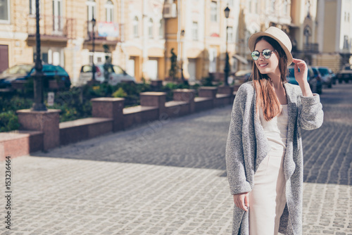 Fotografía  Happy young girl on vacation in a stylish hat and sunglasses, wearing pure light