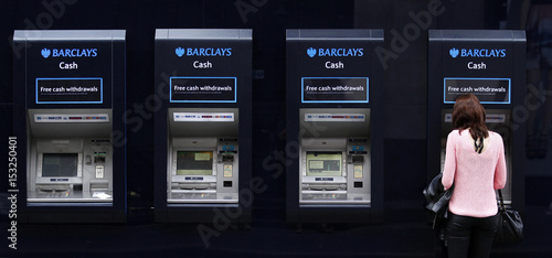 A woman uses one of a line of Barclays cash dispensers in