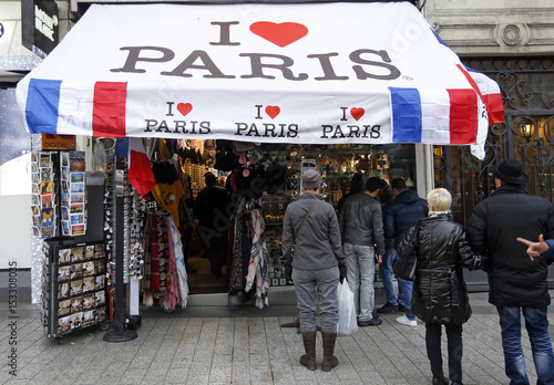 People stand in front of a tourist souvenir shop decorated