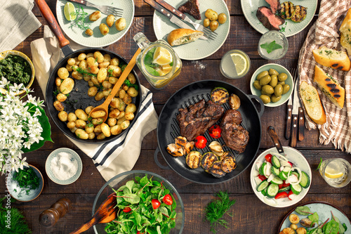 Dinner table with meat grill, roast new potatoes, different food - 153325055