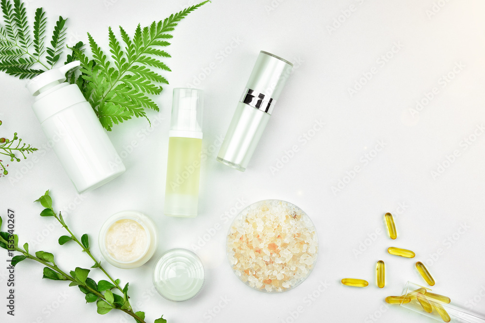 Fototapeta Cosmetic bottle containers with green herbal leaves, Blank label for branding mock-up, Natural beauty product concept.