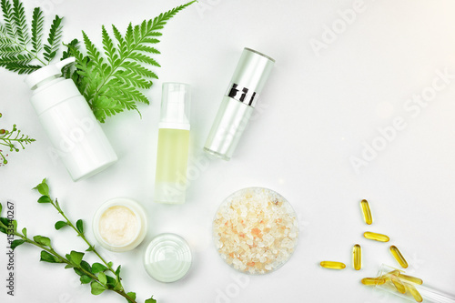 Fotografía  Cosmetic bottle containers with green herbal leaves, Blank label for branding mock-up, Natural beauty product concept