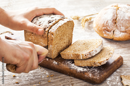 Fényképezés Female hands cutting whole wheat bread