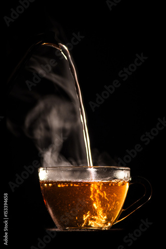 Photo sur Toile The hot tea is poured from pot into glass mug