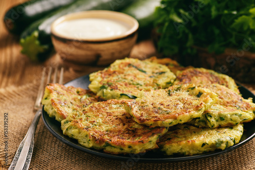 Vegetarian food - zucchini fritters on wooden background. Canvas Print