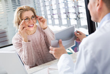 Male Optician Offering Glasses Frames To Elderly Woman