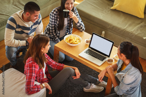 Fotografia  Group of friends sitting together in living room and watching movie on on laptop