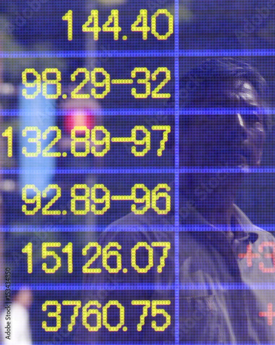 A man is reflected in an electronic board displaying foreign