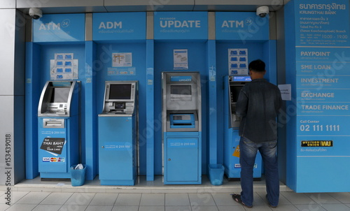 A man uses an ATM machines at the Krungthai Bank in central