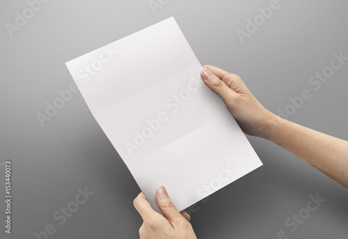 Fotografering  Hands holding paper blank a4 size for letter paper on grey background