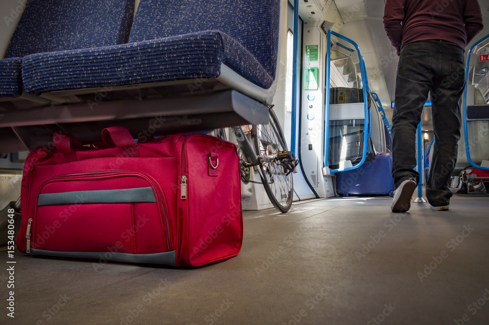 Fototapeta Terrorism and public safety concept with an unattended bag under a chair on a train wagon, monorail or subway cart and man wearing a hoodie walking away from the suspicious item (possibly terrorist)