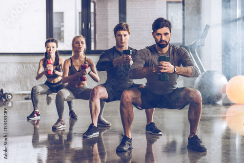 Fotografia Group of athletic young people in sportswear with dumbbells exercising at the gy
