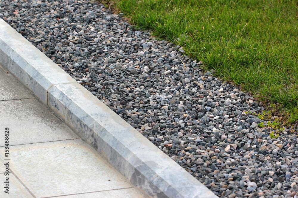 Fototapeta Border kerb between lawn and sidewalk in a park