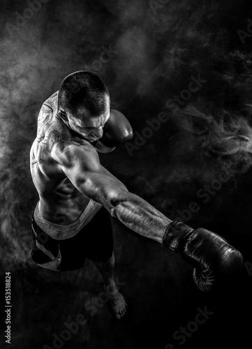 Muscular kickbox or muay thai fighter punching in smoke. Wallpaper Mural