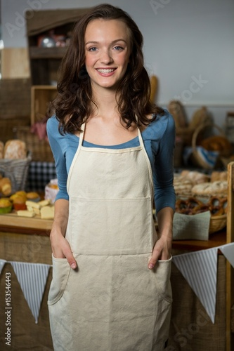 Portrait of female staff standing with hands in pocket - Buy this
