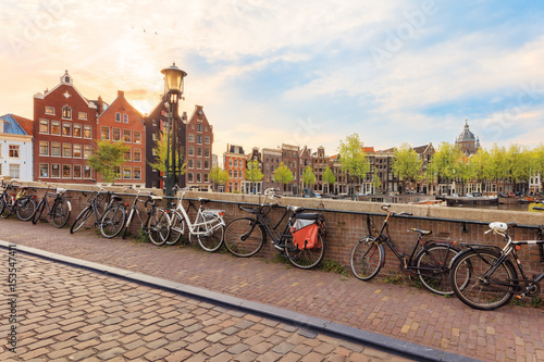 Fotobehang Fiets Canals of Amsterdam. Sunny view of traditional bridge with bicycles